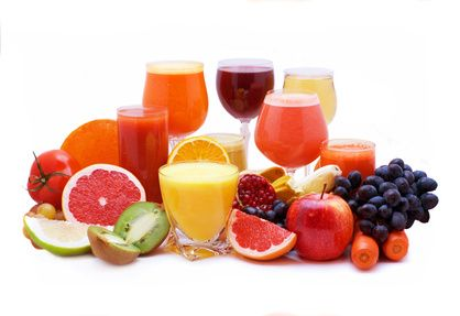Glasses of fruit and vegetable juice with fruits on a white background